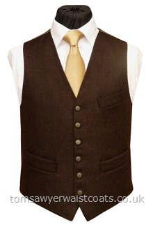 This dark brown tweed waistcoat has a subtle herringbone weave and is made from 100% pure new wool, woven in the UK. This waistcoat features a back and lining in our ginger 'changeant' two-tone polyester twill and has an additional breast pocket and our Low Neck Classic cut. Waistcoat Style- TS434- Fabric- 16oz wool tweed- Colour- Dark brown- Buttons- Antique brass effect- Back & Lining- Ginger 'Changeant' Polyester Twill- You can click here to v....
