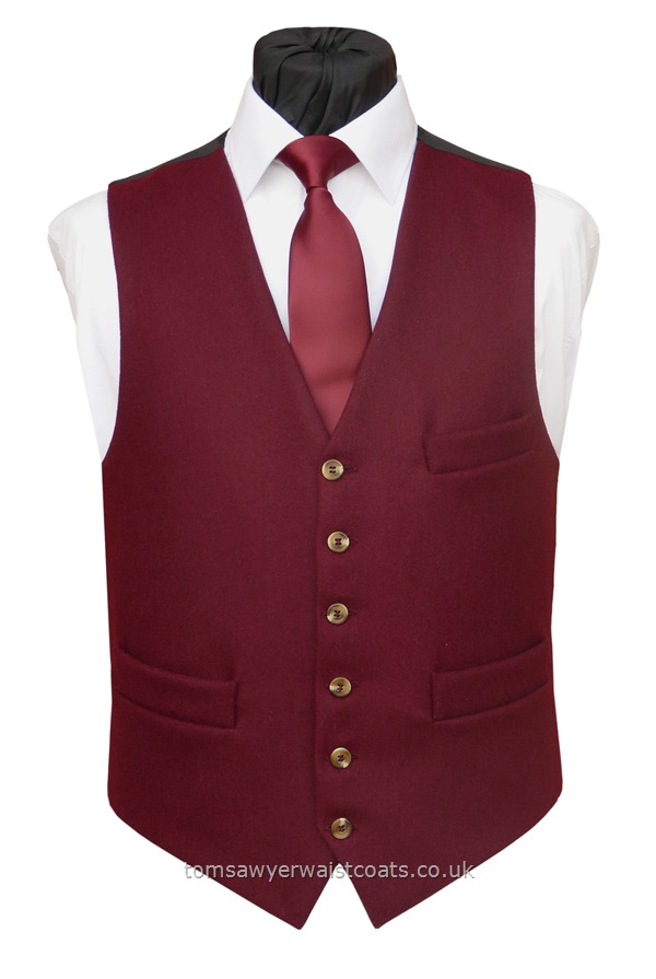 A rich burgundy informal waistcoat in a medium weight lambswool Melton. Featuring a lower cut, shaped neckline and additional breast pocket. Waistcoat Style- TS248- Front Fabric- Melton Wool- Colour- Burgundy- Buttons- Tortoiseshell Colour- Back & Lining- Black Polyester- - Please choose the size you require.You can click here to view our size chart to help you decide.