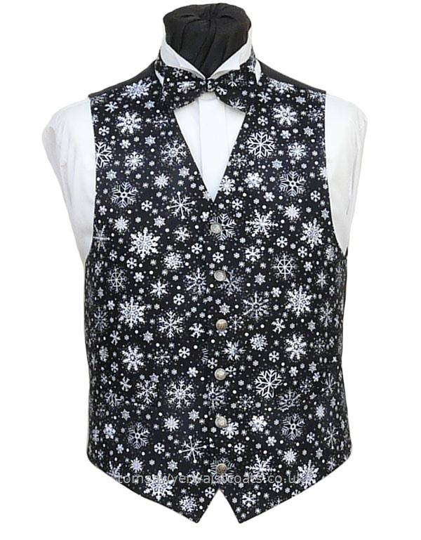 Small white snowflakes on a slightly mottled black background make this a smart Christmas waistcoat. Waistcoat Style- TS554- Front Fabric- 100% Cotton- Colour- Black and White- Buttons- Silver Patterned- - Back & Lining- Black polyester- You can click here to view our waistcoat size chart. Featured shirt White Wing Collar Shirt-