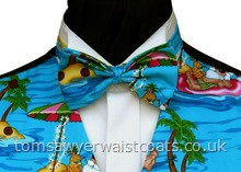 This pre-tied bowtie features the 'Santa's Tropical Holidays' print, jolly Santas and reindeer relaxing under palm trees on an aqua blue background. Style- Ready Tied Bowtie- Fabric- Cotton- Colour- Multi on aqua blue background-